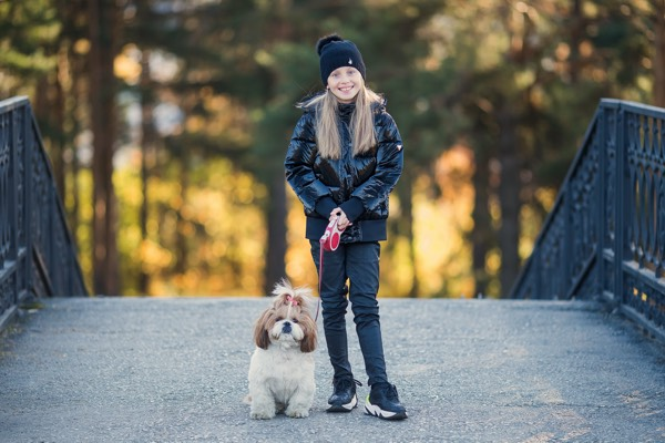 Cute little girl in a black coat with a dog walk in the park. A child is training a dog. Faithful friends of man. Leisure with your pet
